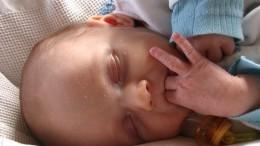 Un bébé suce ses doigts