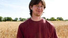 Un jeune agriculteur devant son champs de blé