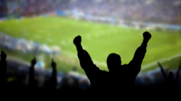Homme joyeux devant un stade de foot