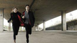 Un couple se tenant par le bras entrain de courir